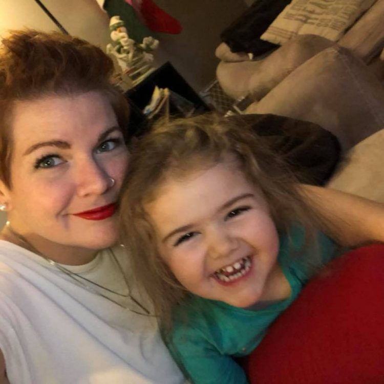 Mother and daughter smiling at camera, mother is laying down