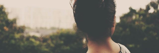 woman with brown hair in a bun looking out over trees