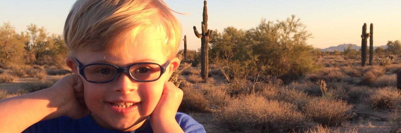 Little boy with Down syndrome smiling. He wears a blue shirt, glasses and has blond hair.