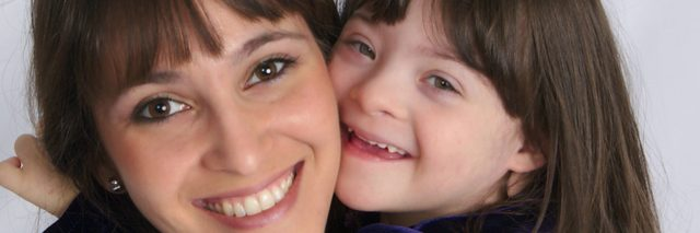 Mother hugging daughter with Down syndrome, face close up.