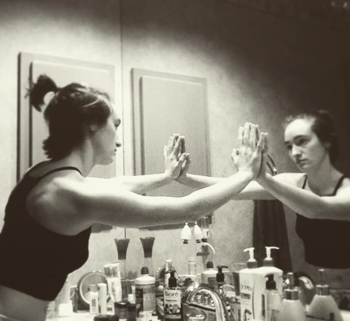 woman with hands pressed against her mirror