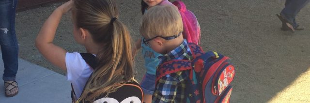 Three children holding hands walking into school, in the middle is a little boy with Down syndrome