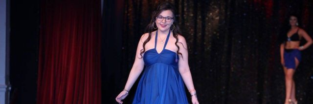 A photo of the writer walking down the runway in a beautiful knee-length blue dress.