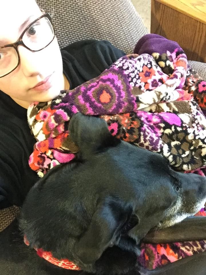 woman lying on the couch covered in blankets and sitting with her dog