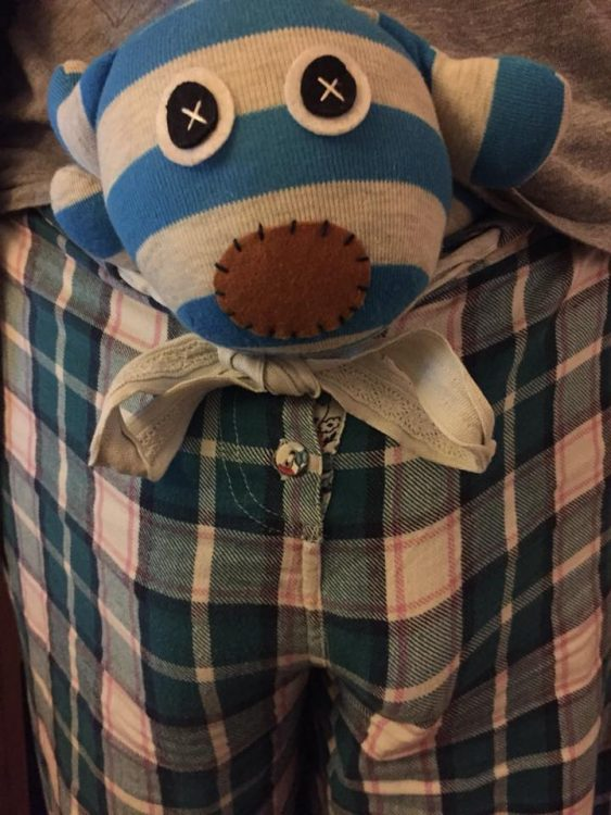stuffed animal in front waistband of plaid pajama pants