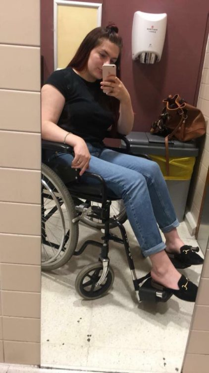 woman in wheelchair taking photo of herself in a full length mirror