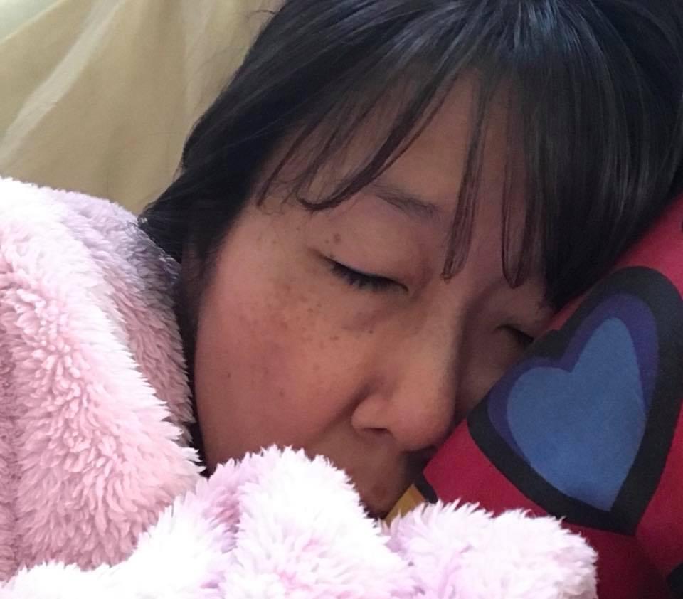 woman sleeping under a pink blanket