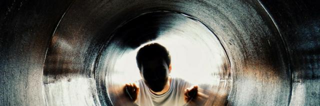 person looking through dark hole