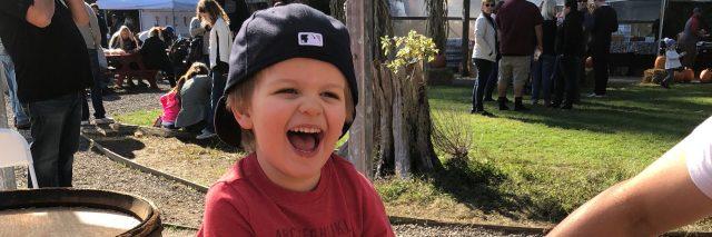 Toddler sitting on hay bale, laughing