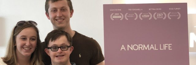 "Alex with his brother and mom standing next to movie poster for ""A Normal Life."""