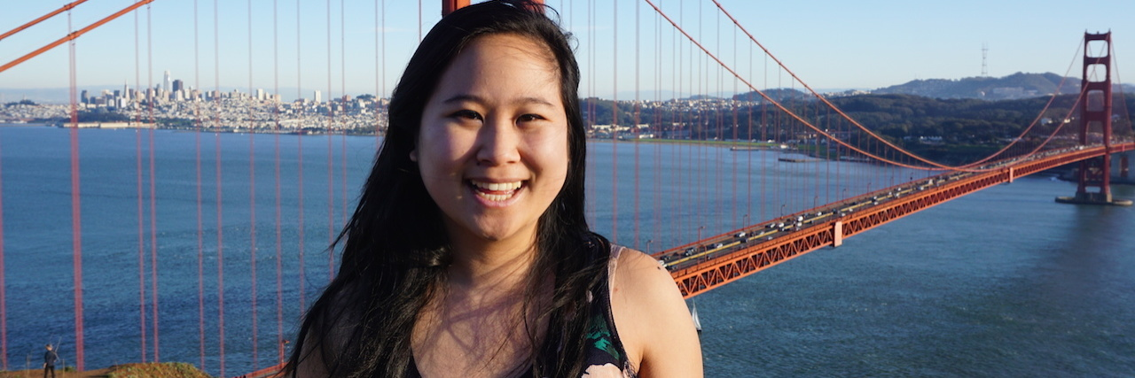 Photo of an asian woman standing in front of the golden gate bridge