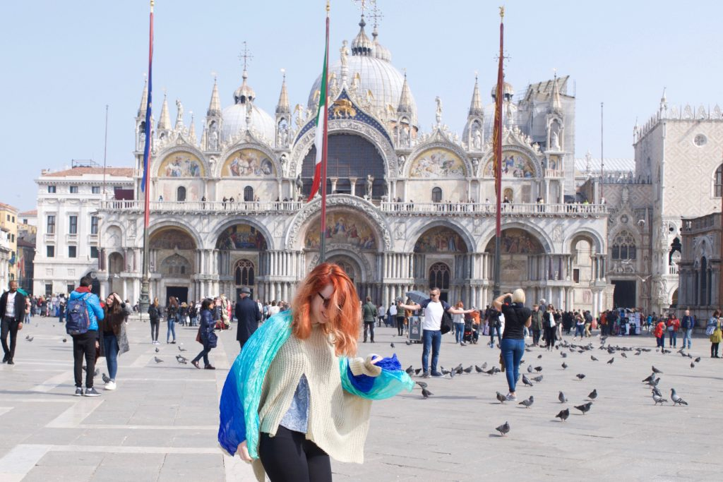 woman with red hair standing in front of a historic building
