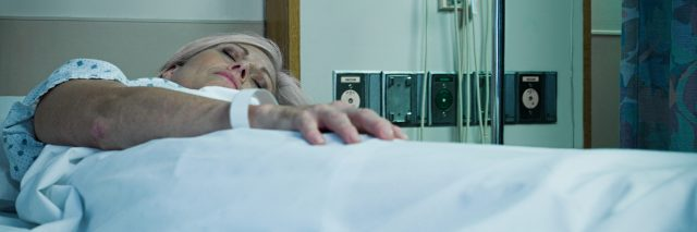 Mature woman lying in hospital bed asleep