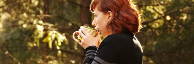 woman standing outside on her porch drinking coffee surrounded by trees