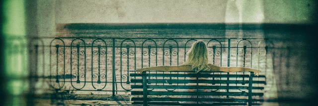 Blond woman sitting on a bench and looking at sea.