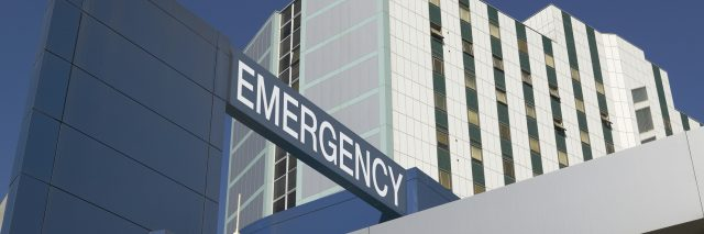 Emergency Sign on Hospital entrance against blue sky