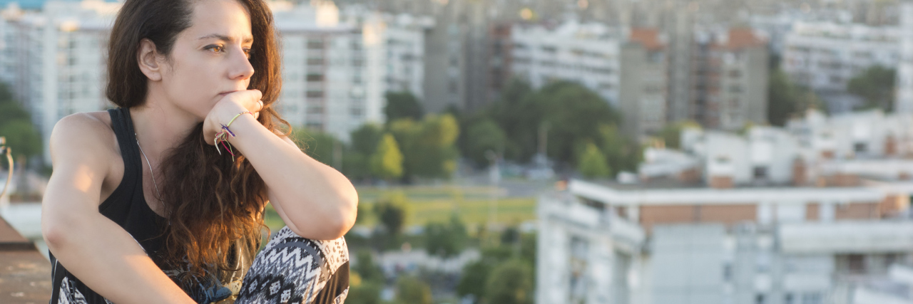 woman sitting on the ledge of a building and looking out at a city