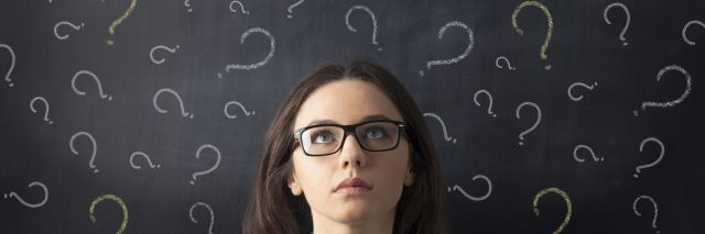 A woman looking up at a chalk board with question marks above her head.