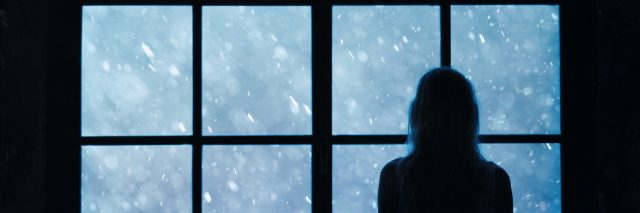 Lonely woman standing and looking out a window
