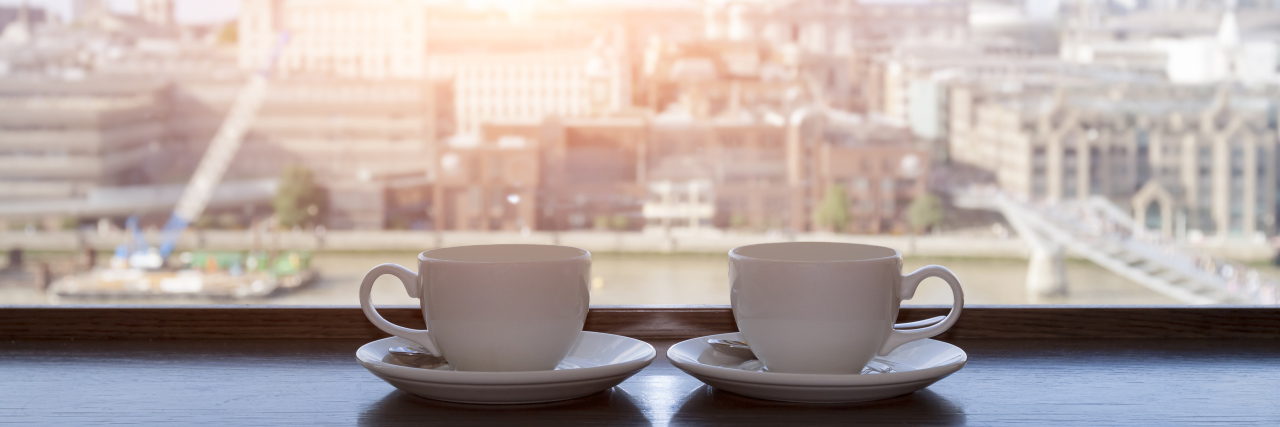 Two cups of coffee with panoramic view of a city in background.