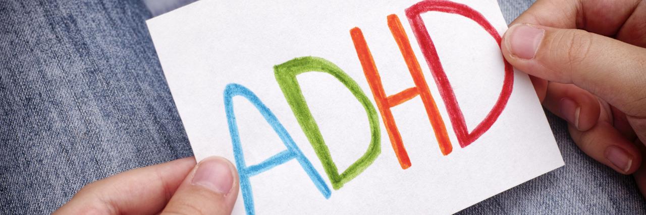ADHD text written on sheet of paper.