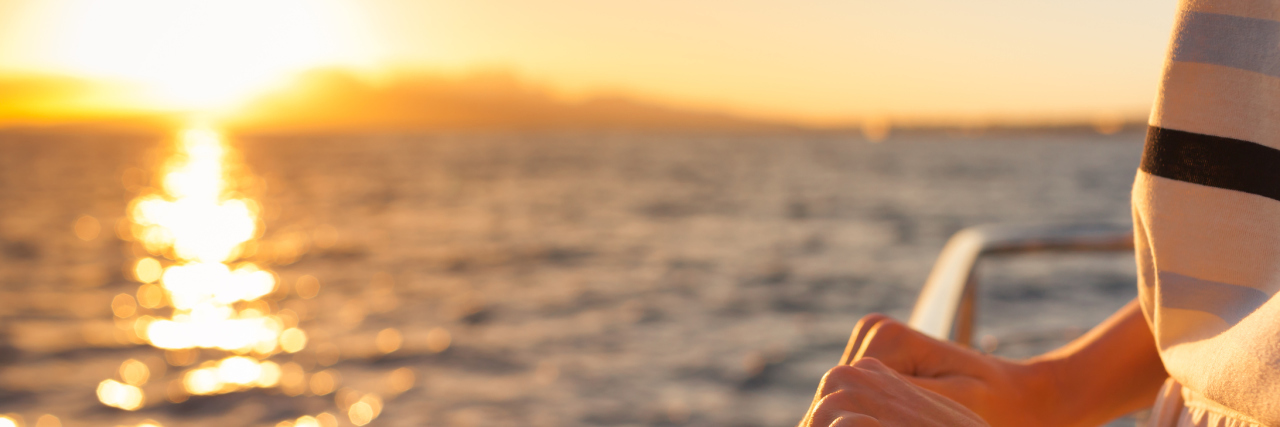woman's hands holding the railing of a boat with the ocean in the background at sunset