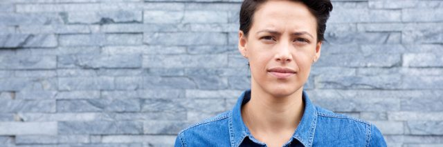 woman with short brown hear wearing a jean jacket and standing in front of a tiled wall looking at the camera