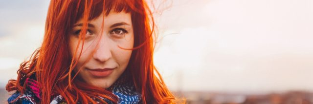 woman standing outside with red hair blowing in the wind
