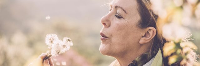 A picture of a middle-aged woman blowing on a dandelion.