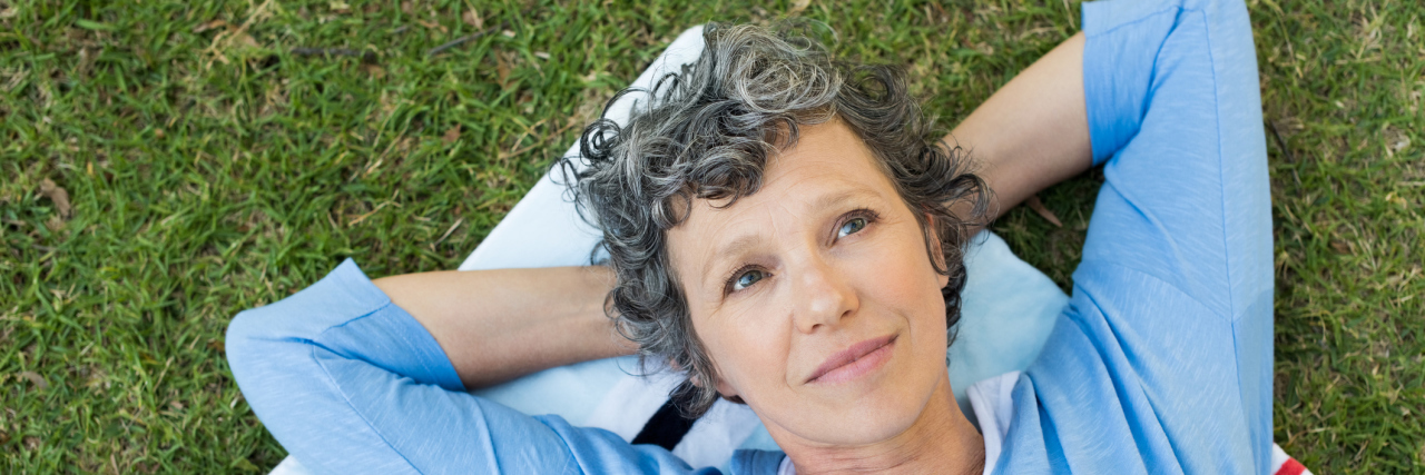 An older woman laying in the grass looking peaceful.