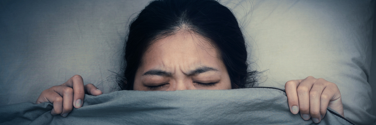 woman lying in bed pulling the covers up over her head