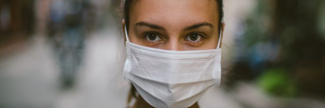 Young woman wearing face mask in the street.
