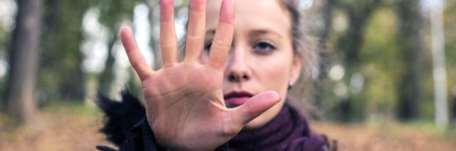 Woman in woods holding hand out in stop gesture