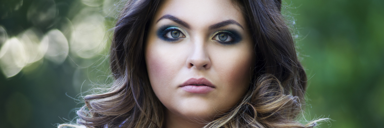 A plus size woman looking into the camera with a serious expression.