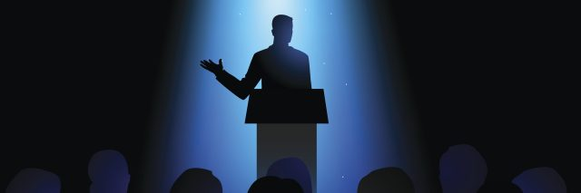 Silhouette of a man giving a speech on stage.