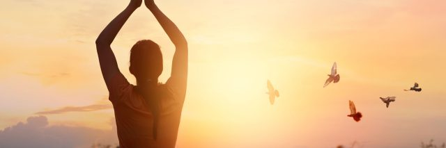woman praying outside at sunset with birds flying overhead