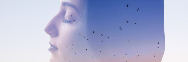 double exposure of a woman with her eyes closed and a sunset with birds flying around