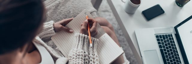 woman curled up on her couch writing in a journal