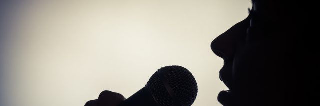Silhouette of a woman singing with a microphone.