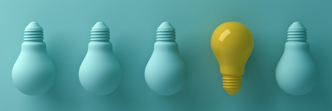 One yellow light bulb standing out from the unlit green incandescent lightbulbs.