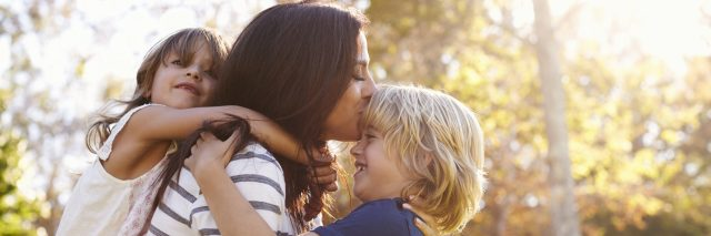 Mother hugging her children in the park.