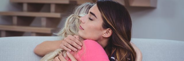 two women hugging each other in support