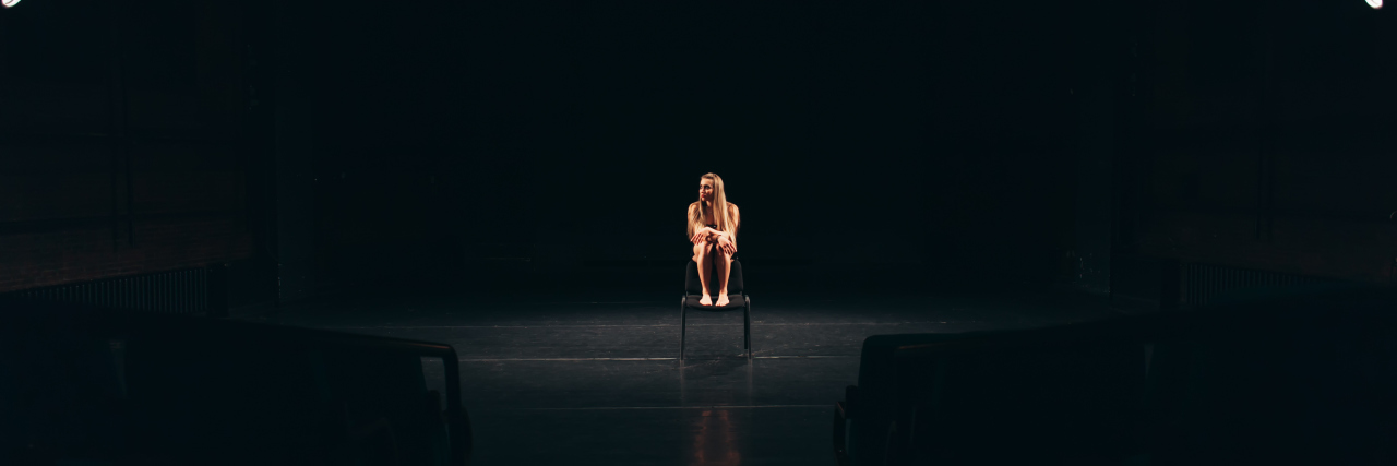 Actress alone on stage sitting barefoot on a chair.