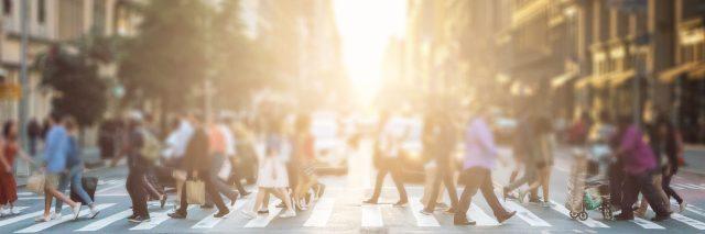 Group of people walking across a pedestrian crosswalk.