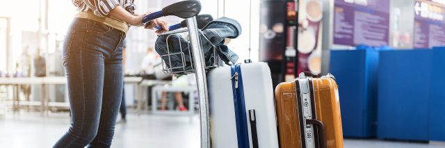 woman pushing cart stacked with luggage through the airport