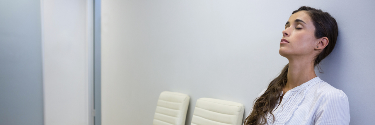 woman sitting in a waiting room with her eyes closed