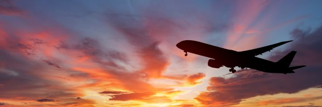 The silhouette of a passenger plane flying at sunset.