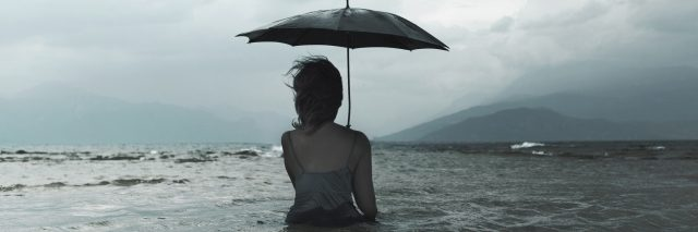 A woman holding an umbrella over her head in stormy weather, while standing in the middle of a body of water that goes above her waste.