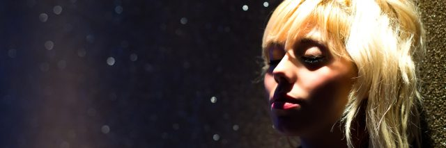A blonde woman in a dark room with her eyes closed.