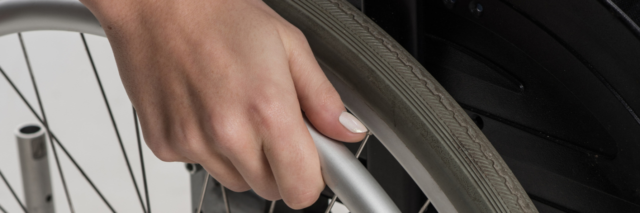 A woman with painted nails with her hand on the wheel of her wheelchair.
